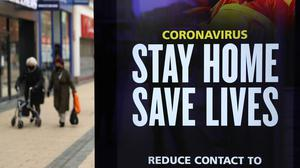 People walk past a 'Stay Home Save Lives' sign in Bristol during England's third national lockdown (Andrew Matthews/PA)