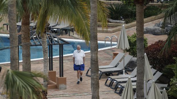 A man walks next the swimming pool of the H10 Costa Adeje Palace in Tenerife (Joan Mateu/PA)