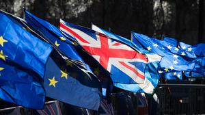 Anti-Brexit campaigners wave Union and European Union flags outside the Houses of Parliament, London.