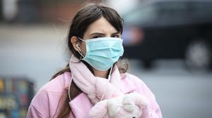 A woman wearing a face mask in Leeds, West Yorkshire, the day after Prime Minister Boris Johnson called on people to stay away from pubs, clubs and theatres, work from home if possible and avoid all non-essential contacts and travel in order to reduce the impact of the coronavirus pandemic.