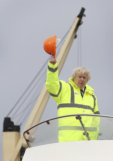 Prime Minister Boris Johnson waves his hard hat as he travels aboard a boat on the River Tees during a visit to Teesport in Middlesbrough (Scott Heppell/PA)