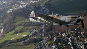 A Spitfire flies over the Battle of Britain Memorial in Folkestone, Kent, in a tribute to the fallen (PA)