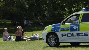 Police officers in a patrol car move sunbathers on in Greenwich Park, London (PA)