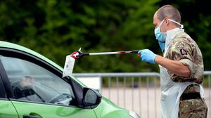A person passes a completed coronavirus self-test package through a car window (Nick Ansell/PA)