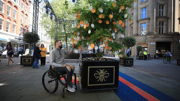 Martin Hibbertt, who suffered life-changing injuries in the Manchester terror attack, reads messages left on a 'Tree of Hope' in St Ann's Square, Manchester (Peter Byrne/PA)