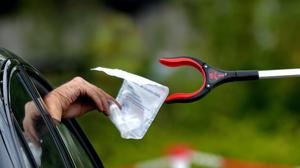 A person passes a completed coronavirus self test package through a car window (Nick Ansell/PA)
