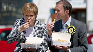Nicola Sturgeon and Stephen Gethins eat chips on the General Election campaign trail (Jane Barlow/PA)