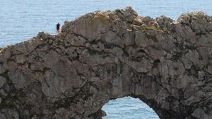A person stands on the rocks above the sea at Durdle Door, near Lulworth, despite Dorset Council announcing that the beach was closed to the public after three people were seriously injured jumping off cliffs into the sea (PA)