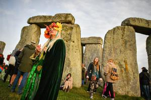 A woman wearing a colourful head-dress at Stonehenge during the 2018 Summer Solstice (Ben Birchall/PA)