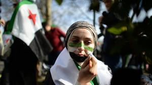 A protester, campaigning in London for more international involvement in Syria, as it was revealed more than 76,000 people died in the conflict last year.