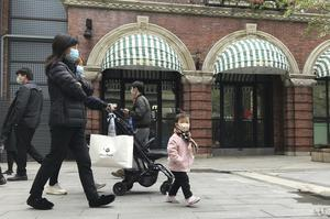 Residents wearing masks visit a shopping street in Wuhan in central China's Hubei province (Olivia Zhang/AP)
