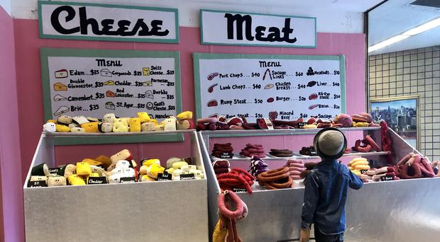 A boy at the meat counter of Lucy Sparrow's Delicatessen On 6th in New York (Claire Hayhurst/PA)