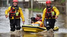 Rachel Cox, with her dog, is rescued after flooding in Nantgarw, Wales (Ben Birchall/PA)