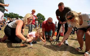 Competitors try to coax the most worms out of the ground during the World Worm Charming Championships at Willaston County Primary School, in Willaston, Nantwich, Cheshire (PA)