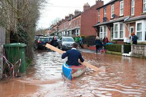A man paddles a kayak on flood water after the River Wye burst its banks in Ross-on-Wye