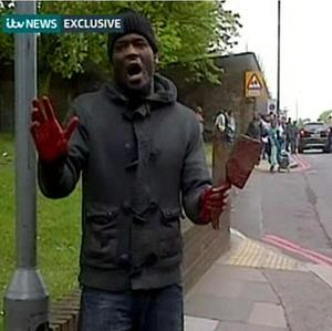 This videograb, from ITV News, shows a man holding weapons by the scene in John Wilson Street, Woolwich (ITV News/PA)