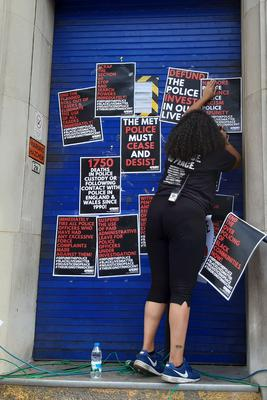 A protester hangs posters during the rally (Helen William/PA)