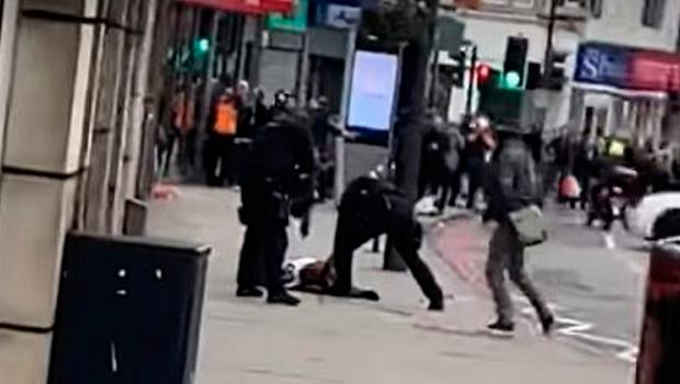 Armed police officers surround a figure on the ground in a video recorded by an eyewitness