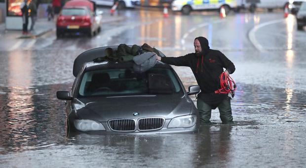 A man with car in a flooded street Sheffield (Danny Lawson/PA)