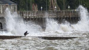 A man takes a photograph of the waves in Dawlish, Devon (Steve Parsons/PA)