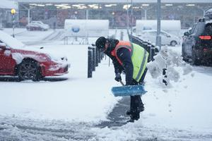 A member of staff from Tesco shovels snow outside the store in Hexham, Northumberland (Owen Humphreys/PA)