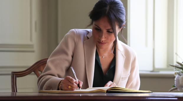 The Duchess of Sussex signs the visitors' book as she and the Duke of Sussex visit Edes House in Chichester (Daniel Leal-Olivas/PA)