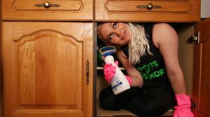 Circus contortionist Stephanie Bates squeezes herself into a kitchen cabinet at her home in London (Jonathan Brady/PA)