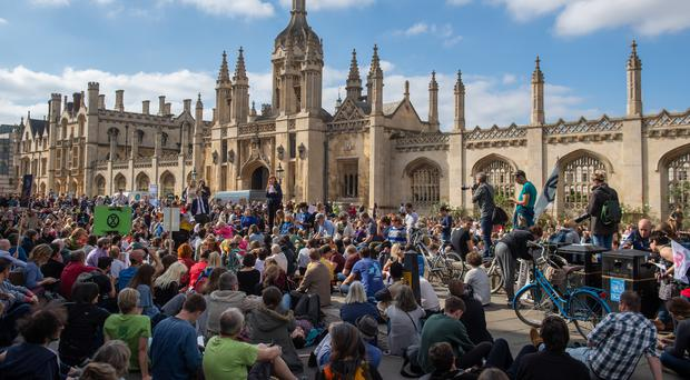 Protestors sit down in the street in front of King's College Cambridge (Joe Giddens/PA)