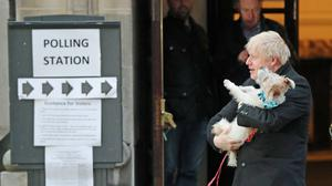 Prime Minister Boris Johnson holds his dog, Dilyn, after casting his vote in the 2019 general election (PA)