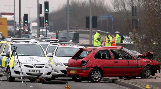 The wreckage of a red Ford Fiesta remains at the scene of a fatal accident on the A33 in Reading, Berkshire