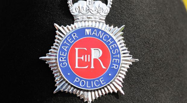 Two Greater Manchester Police officers were injured when a vehicle they had stopped was driven into them