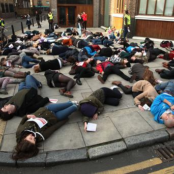 Students from around the UK lie on the ground during an Amnesty International 'die-in' protest, to illustrate the impact of the poorly regulated arms trade, at Amnesty International Human Rights Action Centre in central London. PRESS ASSOCIATION Photo. Picture date: Saturday March 2, 2013. Photo credit should read: Yui Mok/PA Wire