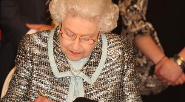 The Queen signs the Commonwealth Charter at a reception at Marlborough House