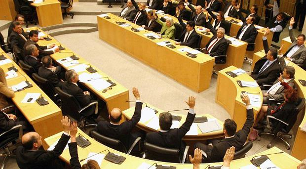Members of parliament vote against a crucial plan to seize a part of depositors' bank savings, in Nicosia, Cyprus (AP/Philippos Christou)