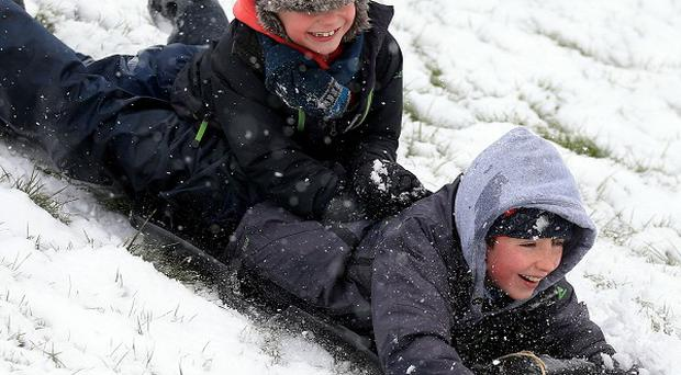 Daniel and James Egerton play on their sledge in the snow in Bingham, Nottinghamshire