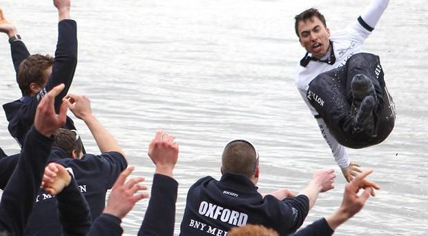 Oxford's cox Oskar Zorrilla is thrown into the river by his teammates