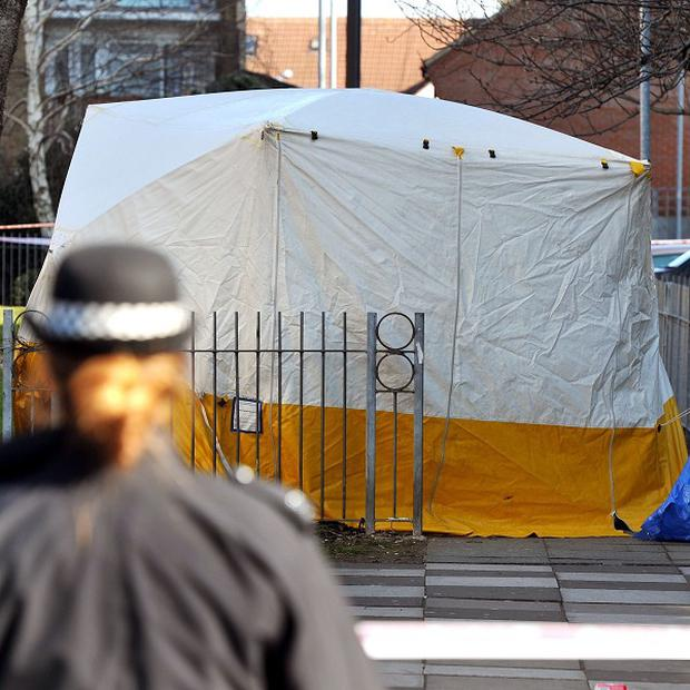 A police officer stands close to a tent after a 19-year-old man died after he was found injured in Edmonton, following reports of shots being fired