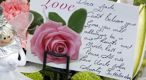 Dozens of floral tributes were left outside the home where 14-year-old Jade Anderson was mauled by a pack of dogs