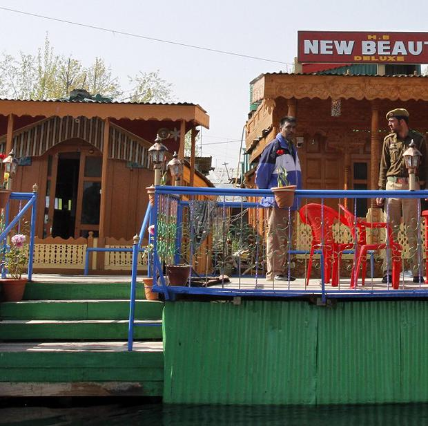 A policeman stands guard outside a houseboat where a female British tourist was found dead on the Dal Lake in Srinagar, India (AP)