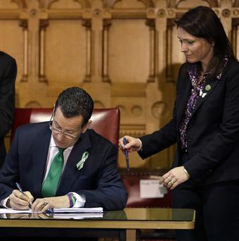 Nicole Hockley, right, watches as Connecticut governor Dannel Malloy signs legislation that includes new restrictions on weapons (AP)