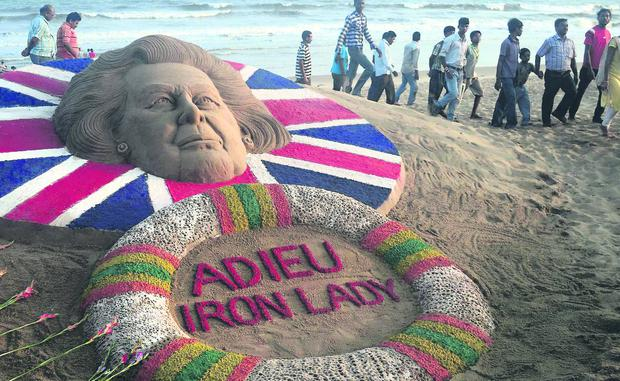 Indians look at the sand sculpture of former Britain's Prime Minister Margaret Thatcher made by Sudarshan Pattnaik, as a mark of homage, at the golden beach of Puri, about 67 kilometers (42 miles) away from the southeastern Indian temple city Bhubaneswar, India, India, Tuesday, 09 April 2013. (AP Photo/Biswaranjan Rout)