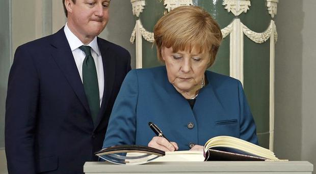German Chancellor Angela Merkel signs the guestbook as she welcomes David Cameron to Schloss Meseberg (AP)
