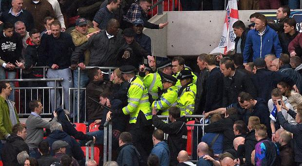 Police deal with fighting Millwall fans during the FA Cup semi final at Wembley Stadium
