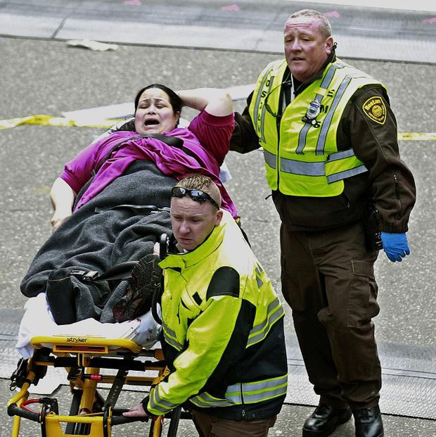 An injured woman is taken from the scene at the finish line of the 2013 Boston Marathon (AP)