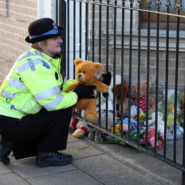 A PCSO lays a tribute from a member of the public outside a flat in London Road South, Lowestoft