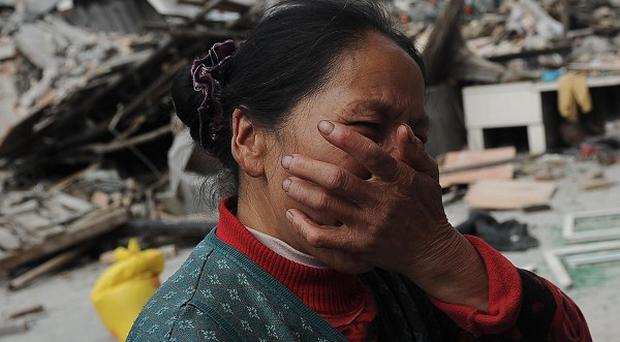 A village woman reacts after her house was damaged by an earthquake in Lushan county, Ya'an, south-west China (AP)