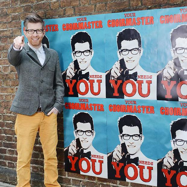 Gareth Malone pasting up 'Your Choirmaster Needs You' posters around the streets of London (Decca Records/PA)