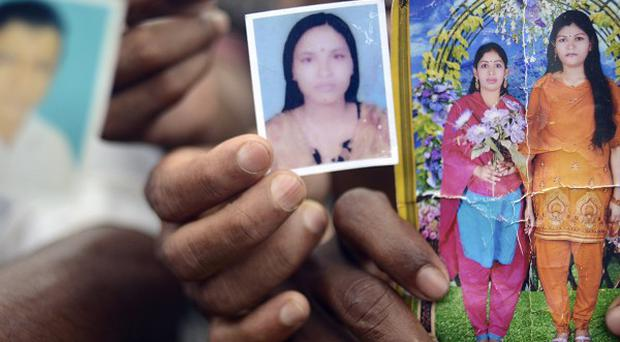 Family members hold portraits of their missing friends and family in Savar, near Dhaka, Bangladesh (AP)