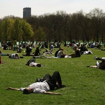 People enjoy the warm weather in Green Park, central London (PA)