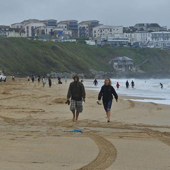 An investigation is under way following the death of a tourist on a popular beach in Newquay